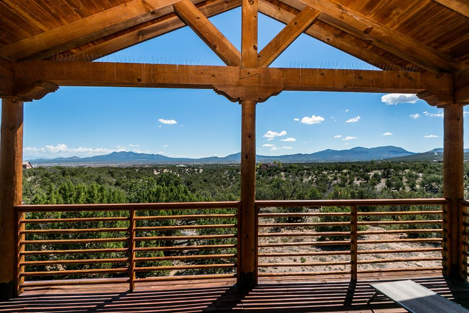 What a price for this prestigious community!! Prideful ownership is prevalent in this custom Northern NM style home. Seldom used pet free home. Enjoy 360 degree scenic views of Mountains and distant city lights of Santa Fe. All living spaces and master on 1 level including a large separate den/study. The home is appointed with SW accents, tongue & groove wood ceilings, kiva fireplace, nichos, and adobe accent walls. Pella wood casement windows, large open great room dining combination. The country kitchen has maple cabinetry, corian counters, and a kitchen bar. Two Large Guest or 2nd Master bedrooms with 2 baths upstairs. Enjoy the covered VIEW deck to see for 100 miles or for star gazing at night. Enjoy the perks of country living with trails and open space nearby.