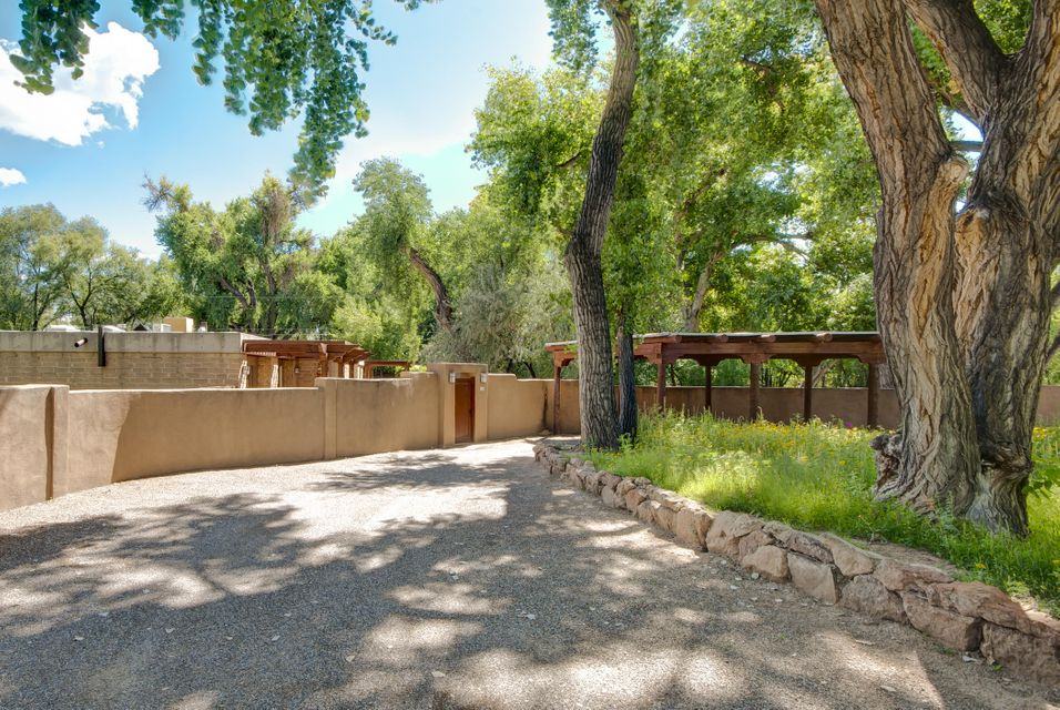 This gorgeous partial adobe near the Corrales bosque sits on a beautiful east-side, tree-lined street. Home has contemporary feel w/ beautiful light, high tongue & groove beamed ceilings & abundant charm. Recently updated kitchen features granite counter tops & extraordinary views of the pond & lush gardens. Separate in-law suite has den, 3/4 bathroom w/ copper sinks, efficiency kitchen, separate entrance & private portal. Spectacular gardens & zen-like setting features a lovely pond w/ lotus blossoms, water lilies & graceful trees. Wonderful flow w/ living room opening through glass doors to spacious family room & screened-in porch for relaxing on warm summer nights. Numerous portals take full advantage of the gracious, lush outdoor space. Property has 2 wells. Corrales at its finest!