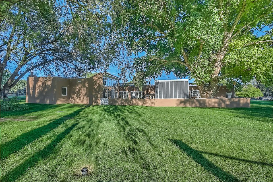Exceptional Corrales Estate! Santa Fe style adobe sits on 2.75 gorgeous irrigated acres w/ MRGCD. Original home dates back to 1936. Updates & additions 1987. Private gunite pool & spa, 8 car garage, horse facilities, screened in porch, tree lined gated entry. Lush park like setting w/mature trees & 100 year old cottonwood. The 4250 sf adobe home features 4/5 BR's, 3 Baths in main, 4th in garage for pool access. Brick & pine wood flooring, beautiful vigas, latillas, T & G  ceilings thru out.  Generous size living areas, formal dining room as well as kitchen dining area. MBR suite features a solar room w/spa, 4 BR's have kiva FP's. Recent updates include new roof,septics, 2 HVAC units w/refrig a/c & pool resurfaced, new cover, &  equip. Country living minutes away from  everyday convenience