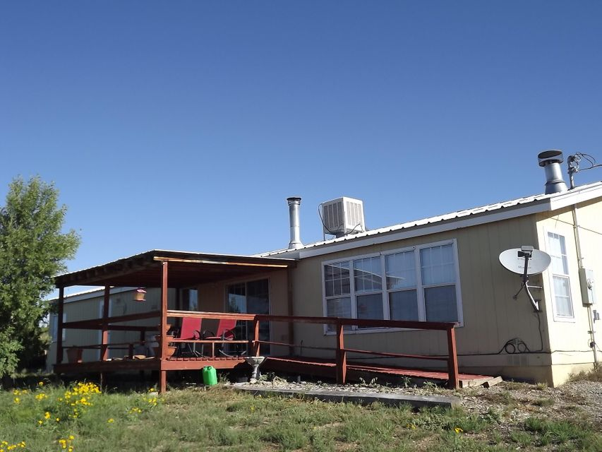 This country home on 4 acres near Moriarty and Edgewood, New Mexico, is on a partially wooded lot and a good county maintained paved road. This is your easy commute to Albuquerque or Santa Fe. Owner financing is offered with attractive terms and a significant down payment of at least 20%. This 3 bedroom, 2 bath manufactured home has decking in the front and back of the home along with a 1-car over-sized detached garage with a workshop area. Come on out to small town America and let us help you find your dream.