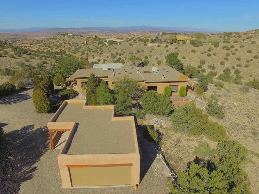 LOOK FOR 3D VIEW OR VIRTUAL TOUR BUTTON.Need a larger rural property with horse potential, but are still organizing your finances? Owner says he will finance this Placitas home on a 5yr balloon note at 6%. He is willing to take only 5% down. Buyer needs to show strong employment with a good steady income & a solid plan for getting finances in order. This custom home is 2,950sf with 2 master suites plus an additional bedroom, plus a rec room & office/4th bedroom & full bath. Brick & hardwood floors, together with open woodwork ceilings create a warm southwestern feel to this home located at the end of a cul de sac & up a winding driveway. The separate building is heated. You even have a small Horse corral. The home is exceedingly private with a commanding view of the Sandia's & valley