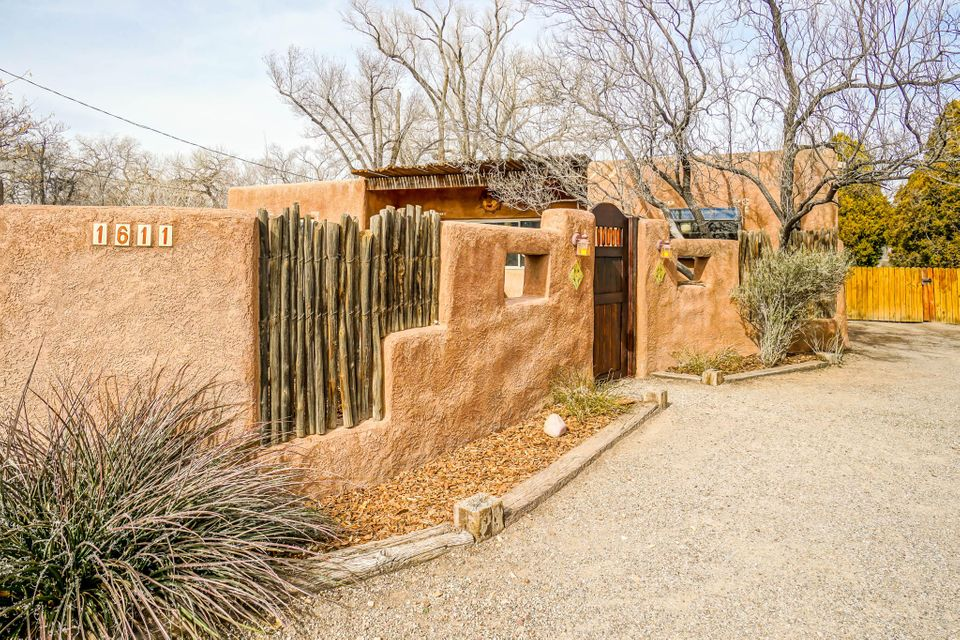 This Vintage Adobe is close to historic Old Town,Bio Park, Rio Grande River, grocery stores, and more. Almost half an acre! The gated front courtyard offers privacy - perfect for entertaining! The cozy living room features a kiva fireplace and viga beamed ceiling. A unique sculptured doorway invites you into the dining room, where a huge window over looks the courtyard. The kitchen features Talavera counter tops, authentic saltillo red & orange hexagonal tile. The kitchen is connected to the den by an internal open window. Another Kiva fireplace is found in the den. Two bedrooms feature viga ceilings. The master bedroom offers a private entrance from outside. Separate workshop / studio. Irrigation well. Home sweet home!