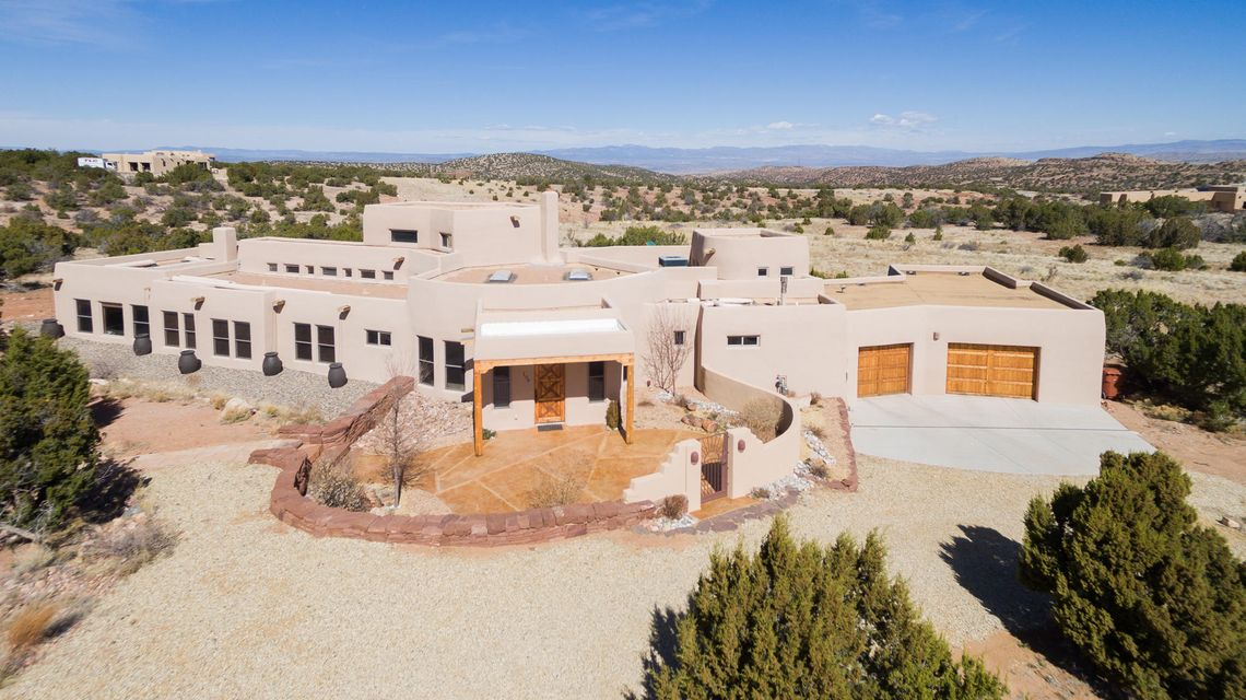 """Santa Fe style home located in Diamond Tail Ranch, a newer, upscale gated community with $1M+ homes, paved roads, underground utilities & access to 55,000 acres of hiking trails. Unique features unlike any other home including: hand-troweled plaster walls throughout the entire home, garage & workshop; architecturally stunning hallway w/ 18 ft cathedral ceiling & exposed adobe; 8 ft hand-carved solid wood doors & travertine flooring; luxurious master suite w/ kiva fireplace, private hot tub courtyard, Kohler claw-foot soaker tub & huge """"California Closet"""" w/ dressing area; gourmet kitchen w/ towering ceiling, chef's pantry, built in SS oven and microwave, built in trash & recycling station, gas range in island & separate eat-at bar, & pull-out shelves. Plz click More link for more info!"""