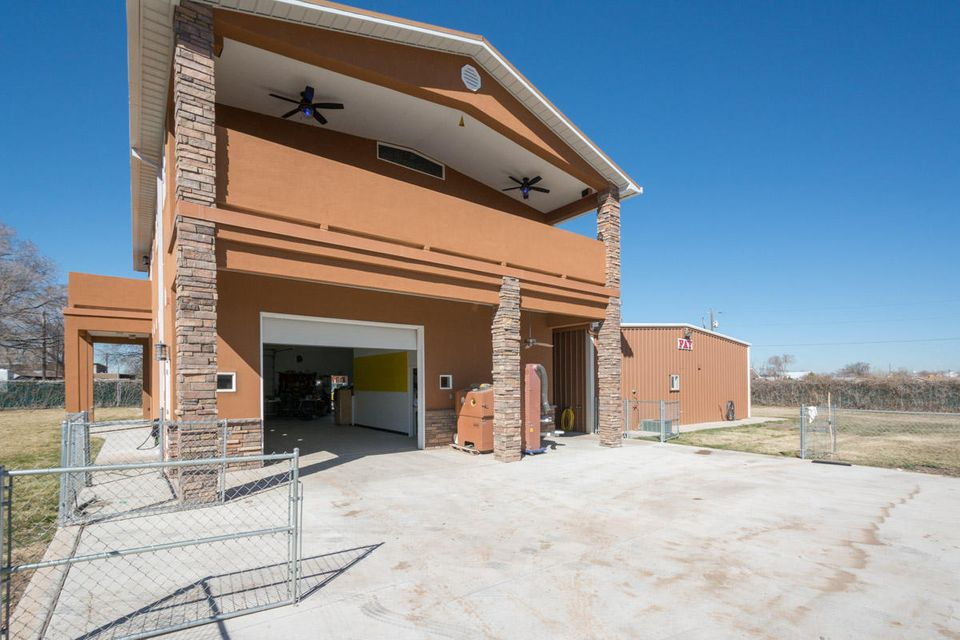 Zoned Agricultural w/irrigation rights. Separate 2 bay 1300 sf heated workshop (NOT in SF) w/apartment. 1500 sf large 3 car tandem garage ground floor (NOT in SF). Backyard access, fully fenced & gated. The house is on 2nd story w/gorgeous views of the mountains & prime viewing for the Balloon Fiesta. Never lived in, this home has 2 balconies, 18'' & wood grain tile, 2 full bathrooms, large kitchen living area w/custom cabinetry & pendent lighting over kitchen bar. Refrigerator & microwave convey. Large Master is stubbed for electric laundry & there's a gas & electric laundry area in downstairs garage. Roof is wired for solar, garage is plumbed for radiant & has a half bath. Workshop's apartment has a bedroom, bathroom, kitchen/living., laundry & storage. Large lot, endless possibilities!