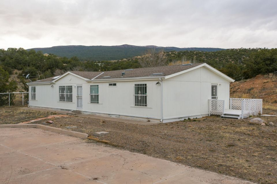 OPPORTUNITY to own a piece of Mountain Tranquility tucked in quiet valley while only 8 min to Albuquerque.  LIGHT & AIRY Open Floor-plan with vaulted ceilings and skylights 2.3 acres with trees and meadow, equipped with irrigation well and CITY WATER. 4BR/2BA well maintained home needing a few updates.  Formal Liv Area, Spacious Greatrm/Den , Plenty Of Kitchen,cabinetry,Pantry,tons of storage, Breakfast Bar/Nook,Utility room for WATER SOFTENER and W/D, Large Master Ste,Private Bath W/Garden Tub/Sep Shwr, 4th Additional Bedrm/Office could be INLAW quarters with separate entrance. Property can be subdivided, Wonderful Horse property Make it your own...