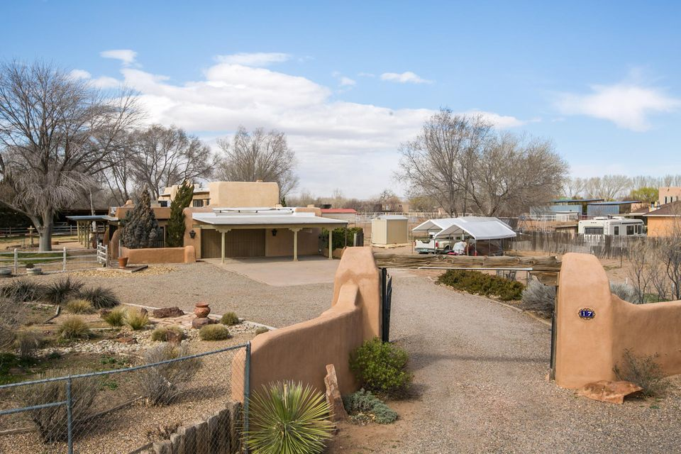 Enjoy the tranquil countryside of this custom SW style adobe home.Settled on 3 acres this home is minutes away from Abq. Featuring 22,000 handmade adobes,passive solar,exposed wood beams,clerestory windows,brick flooring,Rumford style kivas,wood burning fireplaces, playroom/loft & catwalk. Large master suite includes walkin closet,kiva fireplace & vigas. 2ND & 3RD bedrooms are connected by''loft''style playroom. There are 2 living areas,dining area,sun room,cellar/basement, gourmet style kitchen stainless appliances & breakfast bar. Attached in law quarters with private entrance.Large covered patio with courtyard that faces south. Property includes 3 horse stalls,tak room,hay/alfalfa storage,goat pen/birthing room, chicken coop, garden space,large arena for riding/training.
