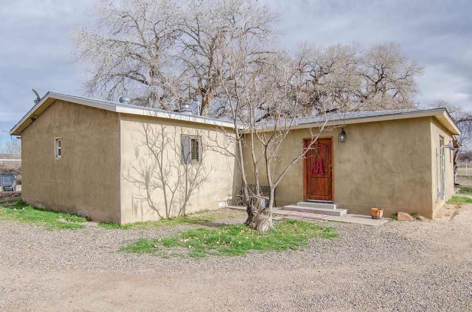 Beautiful country setting, fabulous 1.26 acres, large cottonwood trees and plenty of room for your horses.  Property is waiting for those animals with a large barn, stalls, fully fenced and cross fenced. Real country ambience with wood flooring in kitchen. Anderson windows & refrigerated air conditioning. 2-car detached garage with extra storage space or workshop area. Two wells & RV hook-ups. Easy access to I-25 and minutes to Albuquerque.