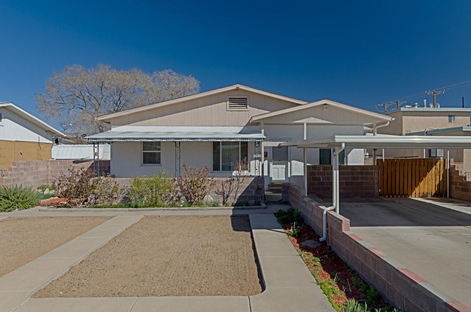 Much loved mid century cream puff in popular area of northeast heights. Real wood floors, new carpet, updated bath, bright & cheery eat-in kitchen, dining room with built in shelves. Large family room with old fashioned style black gas stove. Front living room with wood floors is 2nd living area. The large laundry room is plumbed for a 2nd bathroom. Back yard has access from alley. Separate oversized 1 car garage with work area is air conditioned. Sit on your covered back patio rain or shine and enjoy the flowers and grass. Close to everything, its your own little urban oasis.