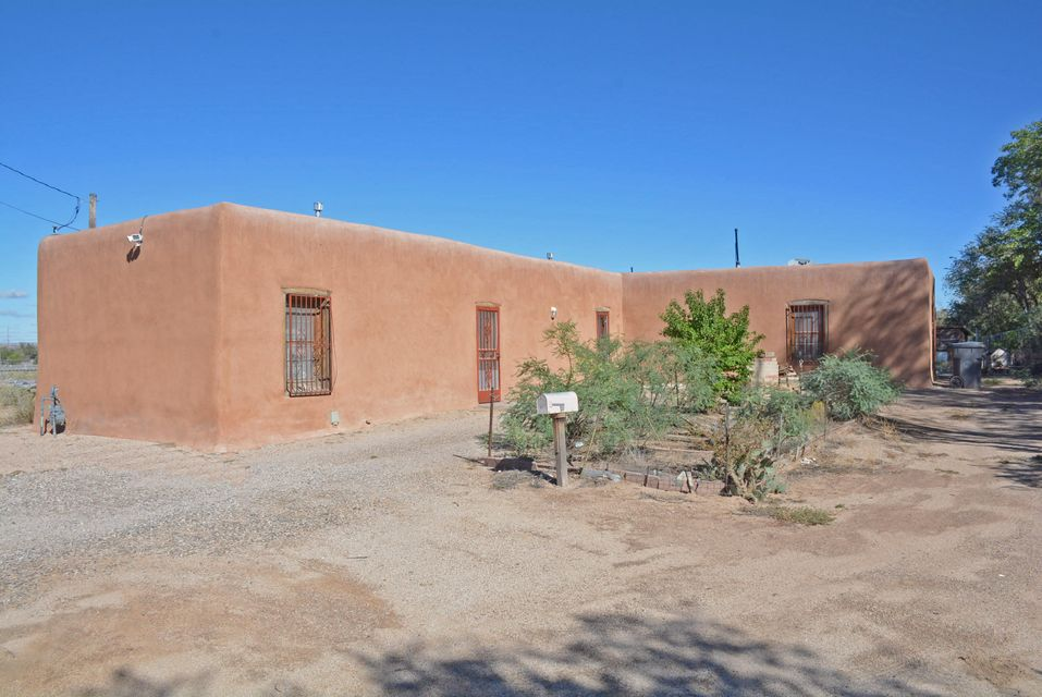 Historic Juan de Dios Chavez house. L-shaped terron house built in a simplified Territorial style which only five similar homes still stand in the city of ABQ. Original beaded wood vigas.  Large country kitchen with freestanding gas heater. Great room, master bedroom with wood burning stove, floor to ceiling closets in 2nd bedroom. Not on the national register. Large 1.65 acre parcel. The overall house plan has remained intact.