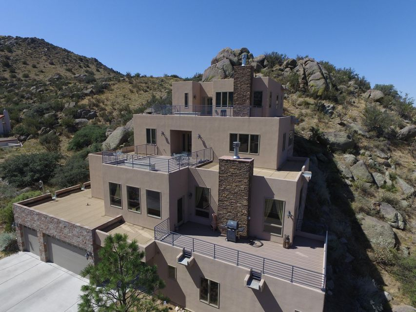 Exquisite custom home with exceptional views in all directions. Backs up to Sandia Foothills Open Space. Step out onto trails that will take you to the top of the Sandia Mountains. Kitchen has birch cabinets, granite counter tops, SS appliances, and 2 sinks. Pella windows and doors throughout. Private Penthouse Master Suite has jetted tub and separate vanities. Second master suite on 3rd floor. And, ground floor office easily converts to another large bedroom. Large rooms throughout feature 3 decks with spectacular views of mountains, city lights, and incredible sunrises and sunsets.