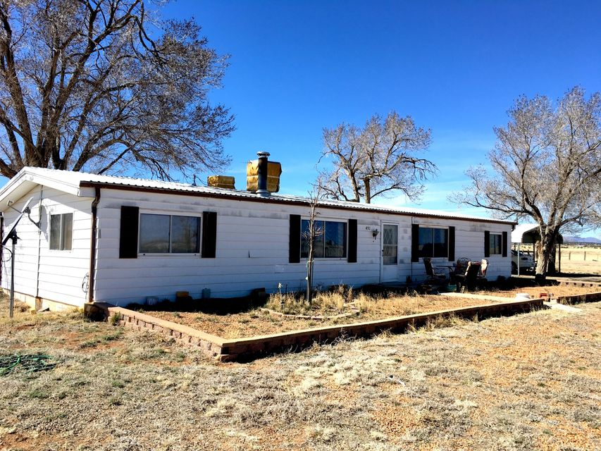 Country home for sale with acreage in central NM. An approximate 35 minute drive west to Albuquerque via I-40; approximately an hour drive north to Santa Fe New Mexico via NM Hwy 41. Close to Moriarty Edgewood Schools. This gem has an older well maintained manufactured home with barns, stalls and pens for your cattle, horses or 4-H and FFA projects. Property is set up for your Recreational or Hobby Ranch with some fencing. More pasture acreage available for grazing. Experience that southwest rural lifestyle here in the Estancia Valley in Central New Mexico. Home is currently offered with 20 acres with up to 60 acres available. Well had a new pressure tank installed in 2014 and a new pump in 2015. The central forced air furnace was replaced about 5 years ago. Home had waterlines replaced.