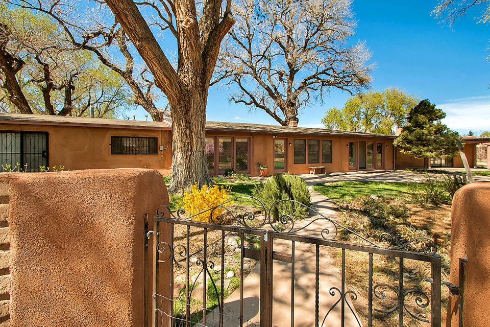 Traditional Corrales home has all the charm you'd expect with a country kitchen, vigas, kiva fireplaces, brick, wood, & tile floors.  Majestic cottonwoods frame the Sandia Mountain views on 2.09 acres. Bosque Preserve & Rio Grande are a short walk away. Separate fenced area for horses, corral, pasture, riding arena. Yard is enclosed with adobe wall and rustic fence. Fruit & nut trees, flower beds, garden area, native shrubs and grass complete the landscaping. Part adobe main house is 2354 sf with 3+ bedrooms & attached in-law quarters is 918 sf with 1 or 2 bedrooms. 1075 sf of covered enclosed entertainment space overlooking the heated gunite pool and 8 ft privacy fence. Sun porches on east and south sides. 2-car detached garage has space for workshop.