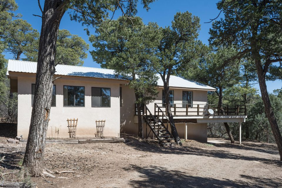 PEACEFUL living in this great home tucked in the pines just 15 minutes from Albuquerque. 3 Bedroom main floor plan, with huge walk-out basement. Lots of windows to view the forested lot, new paint, new carpet, all appliances including washer and dryer. Finished sun-room on upper level, Basement set-up for in-law quarters. Paved road to property. Fully fenced lot. Community water. Deck has been removed due to wear and tear. An allowance of $8,000 is made towards new wrap-around deck. Special loan package to allow for deck construction is available. Call Listing Agent for more details.