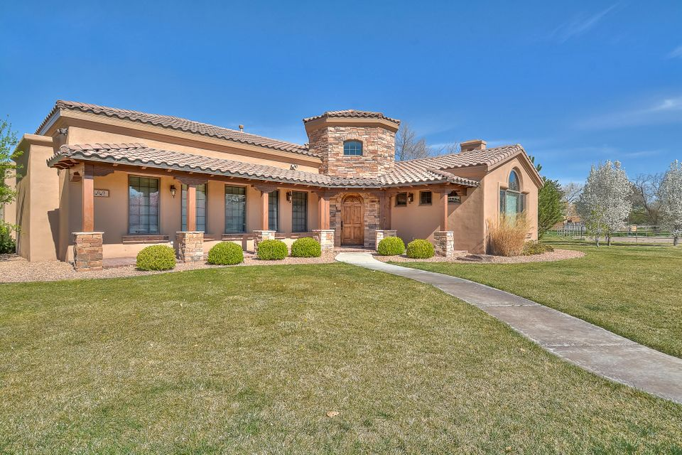 Stunning private ranch located on 2.18  gated acres in Corrales. Built by Joseph Custom Homes featuring 4,162 sf with 3 bedrooms, 3 bathrooms w/ 2 half baths and an oversized 1,534 sf 3 car garage. Rotunda entry way with custom tile work. Living room features oak flooring, wood beamed ceiling and a custom fireplace with stone accents! Gourmet kitchen with detailed Alder cabinetry and crown molding, built in oven and microwave, custom range hood, back splash, granite countertops, 5 burner gas cooktop and trayed ceiling. All bedrooms feature private en-suites! Master suite with outdoor access and trayed ceiling. Bath hosts a deep garden tub, custom vanity with make-up area, massive walk-in closet with built-ins. Active solar system. Impressive mountain views. Full pipe fencing for horses!