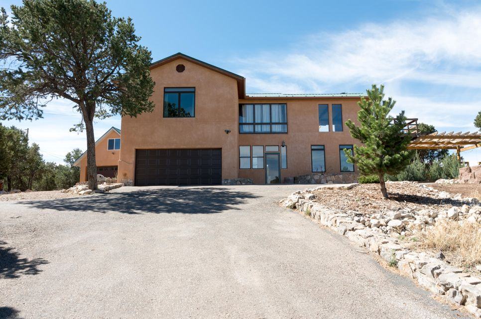 Come see this beautiful custom home in the highly desired Tablazon neighborhood with finished guest house!  This house features wood and tile floors throughout, granite counter-tops, and a stunning two-story fireplace. Enjoy the quiet of mountain living, but with the convenience of being on a paved road with easy access (15 min.) to Albuquerque. Main house is approx. 2355 sq ft and has 4 bedrooms plus an office, 2.5 baths and upstairs laundry! House has refrigerated air for the few times a year you'll want it and central heat complimented by that amazing fireplace to keep warm. Cozy guest house is approx 1035 sq ft with full bath and kitchen and heated by a thermostat-controlled pellet stove. Property has a huge deck to relax on, a playground for kids, chicken coup, & a fenced garden area.