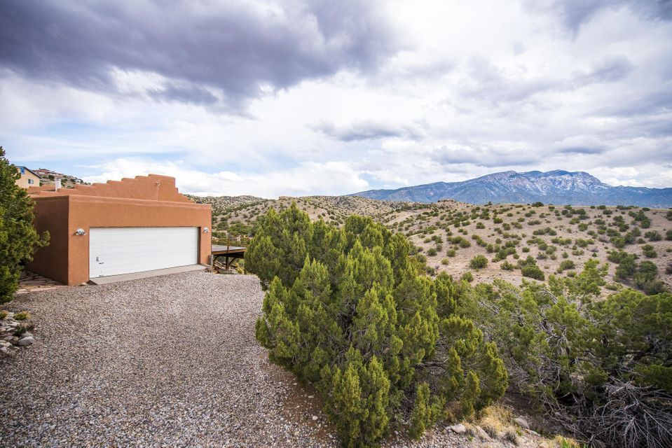 Welcome Home!!  VIEWS!! VIEWS!! VIEWS!! This charming Placitas home is situated on 1.48 acres and captures the amazing mountains views from the living room, bedrooms, and large deck!! Kitchen opens to the main living area for a great open, entertaining room!! Some interior walls have the adobe exposed to give a true southwestern feel with the Kiva fireplace and wood stove!! Ceilings are raised high with windows giving the home passive solar in the winter! Schedule your appointment to visit this lovely home today!!