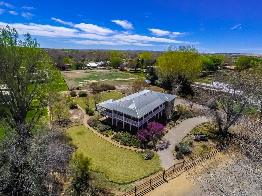 Gorgeous Northern New Mexico-style adobe designed by William Stoddard situated on one of the loveliest Corrales roads near the bosque. This single-owner gem has cherry cabinets, wood-beamed ceilings, brick & hardwood floors & a seamless integration w/outdoor space that features vegetable gardens, apple, pear, plum, peach & cherry trees, flower gardens & landscaping by Judith Phillips. New stucco, new carpet, Pella windows, huge studio/hobby room, re-circulating hot water, garage workshop & passive solar are among the  most outstanding highlights. Come enjoy the views & quiet serenity from two broad verandas (one upstairs & one down) that encircle the home. 14''-thick adobe walls create a quiet, energy-efficient home that embodies the best of New Mexico & captures the magic of Corrales.