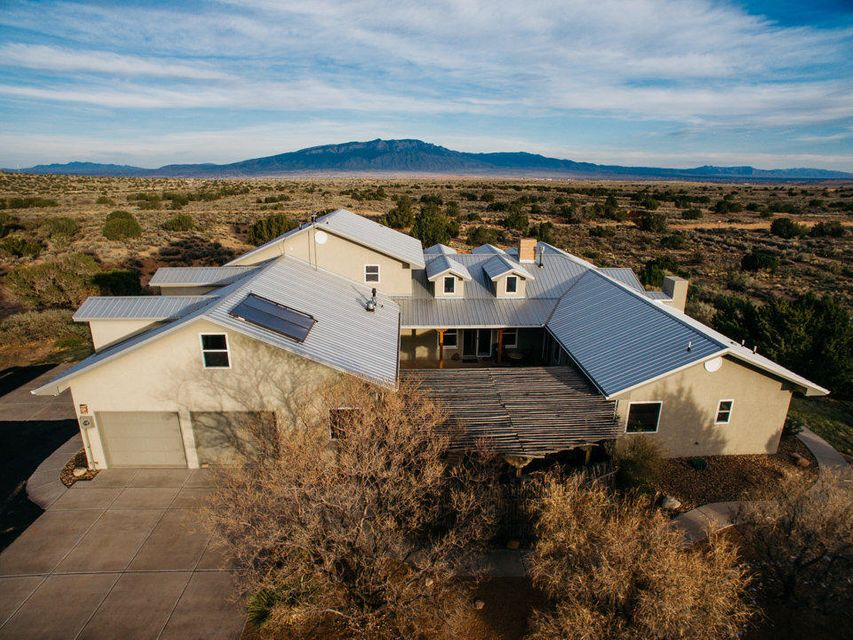 Gorgeous Northern New Mexican Country House on 1.6 acres in North Rio Rancho. 3,189 SF, 3 BR, 3 Bath. Spectacular views of the Sandias and City Lights in a very private setting, Oversized 4-car garage has workshop and loft   Kitchen features Corian countertops, custom hickory cabinets, 2 pantries, island, gorgeous eating area with views, stainless steel appliances.  BR's 2 and 3 are joined by a Jack and Jill bath and could easily be repurposed as an in-law apartment. Large Anasazi style hearth defines the heart of the home.  Country living, yet only 15 minutes to shopping, 6 minutes to the nearest hospital, 2 mins to the Point Grill in Mariposa.  No HOA's, CCR's or PID's.
