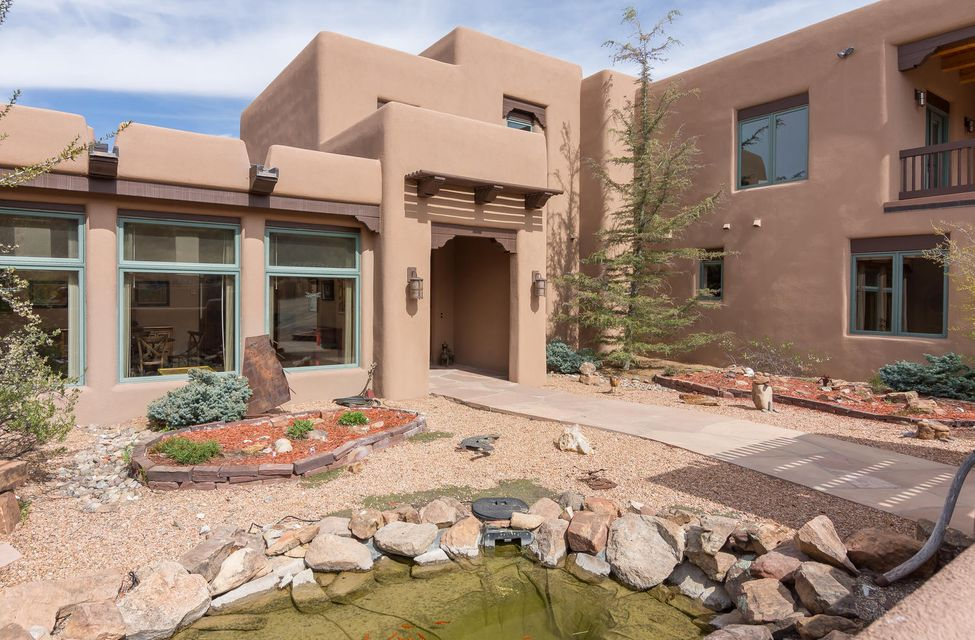 Space and elegance take on a whole new meaning in this flawlessly executed and brilliantly designed SW pueblo-style home. Enjoy ever-changing, panoramic vistas of the Ortiz, San Pedro, Jemez, Sandia, and Sangre De Cristo Mountains. Soaring beamed ceilings, Diamond plaster walls, Italian porcelain tile, custom Alder doors and cabinets, New Zealand  granite, 3-story spiral staircase, morning room, media center, art studio, office, library, wine cellar, & guest casita. Energy efficient, sustainable and more. The builder's own home! Elevate your expectations and enjoy prestigious and gracious living!