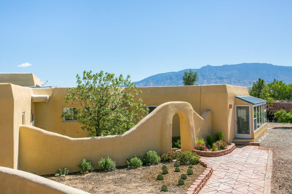 This Enchanting Corrales Compound Offers Some of the Best Sandia Mountain and City Light Views in the Village! All the Classic Charm You'd Expect in a Corrales Home Including  Adobe Construction, Beam Ceilings, 2 Kiva FPs, Brick Floors PLUS Over 3000sqft of Detailed Upgrades! New Refrigerated Air/Heating System w/ Built In Humidifier, New Electrical Panel, New Water Filter, New Wood Flooring,  Upgraded Windows and Window Coverings, Tastefully Updated Kitchen and Baths. A 1352sqft Heated and Cooled Artist's Studio/Workshop w/ 2 Car Garage Crowns the Property and Frames the Breathtaking Views. A Perfect Space for an Artist, Craftsman or Mechanic to Create in a Gorgeous Setting. Detached, Cooled, Oversized 2 Car Garage Sits Adjacent to the Main Home. Gorgeous Grounds and Gardens Surround.