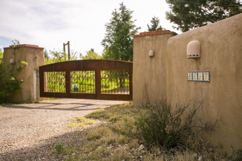Create your own North Valley paradise!  This special offering is a total of approximately 1.9 acres.  1.3 of those acres are preserved in open space used as a spectacular apple orchard.  A charming cottage was built in 2014 with approx 525 sf.  It is one large living/kitchen/sleeping area + full bathroom.  It has a red, standing metal roof, kiva fireplace, custom cabinetry, concrete floors, butcher block top on island, tongue/groove ceiling with beams & a huge workshop & carport.  Perfect for living in while you build your dream home and use it as a guest house!  The seller will cooperate with a replat with the Village of Los Ranchos. Current connection to water supply from Seller's personal residence.  Seller will connect guest house to City water.