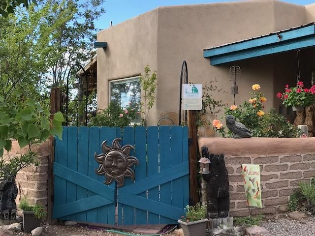 This is a little Gem of a Home w/Gorgeous Outdoor Spaces Certified as a Backyard Wildlife Habitat by The National Wildlife Federation, & it's all on an automatic drip system! The views are of Cabezon, Mesas & Jemez. Enjoy sunsets on the back patio listening to birds sing & fountains tinkling & watching bunnies frolic around, or maybe you'd like to enjoy the evening from the inviting hot tub on the trex deck tucked into the lush landscaping! Vigas & Kiva FP & Saltillo Floors in the Great Room. MBR, KT & Dining Rm have Wood Floors.  Kt has butcher block counter, farm sink, new glass tile backsplash & all new SS appliances. Bathrooms have talavera tiles. There is also a dedicated dog yard w/a dog door from the fourth bedroom. Stucco, roof & parapet have all been refreshed in this Beauty!!