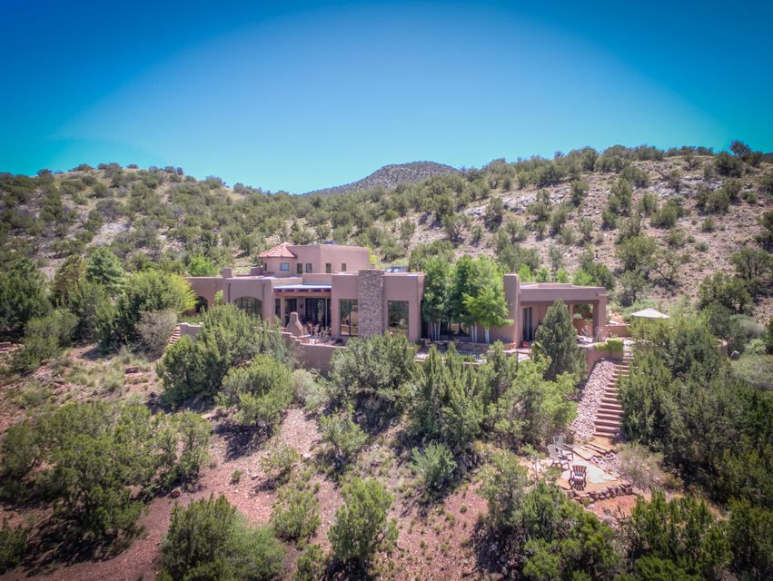 This beautiful estate was built on the Crest of Montezuma, atop one of the highest lots in Diamond Tail Ranch w view of the Jemez, Sangre de Christo and Ortiz Mountains, Cabezon Peak and the lights of Santa Fe! The floorplan was designed w these unsurpassed views in mind. The home features a diamond plaster walled rotunda foyer, travertine floors, raised/beamed ceilings, Sierra Pacific wood windows, 3 custom fireplaces, radiant heating as well as 3 combo heating/refrigerated air units, 75 gallon water heater w/ recirculating pump& a Sodeco water softener & reverse osmosis system. The gourmet kitchen, w/ custom alder cabinetry and granite counters, Wolf & SubZero appliances, chef's pantry & island w/ prep sink & eating area won't disappoint.