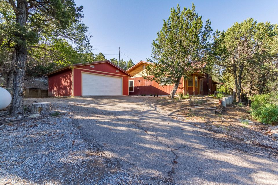 **OPEN HOUSE SUNDAY 5/21 1-4** Lovely private mountain property nestled amongst the trees.  Located in the popular Tablazon neighborhood which offers forest access to some of the best hiking and biking trails in the area, and is only 10 minutes from Albuquerque.  Soaring cathedral ceilings bring in tons of natural light,  2 large living areas with open concept, all on one level. Large kitchen with pantry has updated countertops and tons of cabinet space. Tasteful updates including laminate and vinyl floors and fixtures. Metal roof, wood burning stove, shared well has been redrilled, fenced backyard area and separate 2 car garage. Hurry, this home won't last!