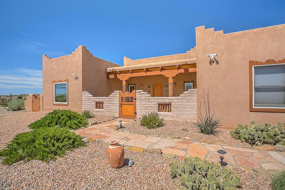 Don't miss this pueblo style move in ready home on 1.1 acres! Inspections/repairs complete. Roof tune-up complete. This home has many custom features including wood ceilings, vigas, kiva fireplace; adobe walls, engraved wood details, custom wood doors throughout, brick floors in living area and tile floors in kitchen, dining, and wet areas. Stainless appliances. Solid surface counters. Double vanity, garden tub, separate shower in the master suite or his/her bathroom setup. Xeriscape landscaping with views of Sandias.  Watch your next balloon fiesta from the south portal!  Back yard access, RV parking,50 amp electrical. Completely fenced.  Enclosed front courtyard.  Covered portal on back with flagstone patio. Converted to natural gas.  Prefer Sandra Johnson at Stewart Title for closing