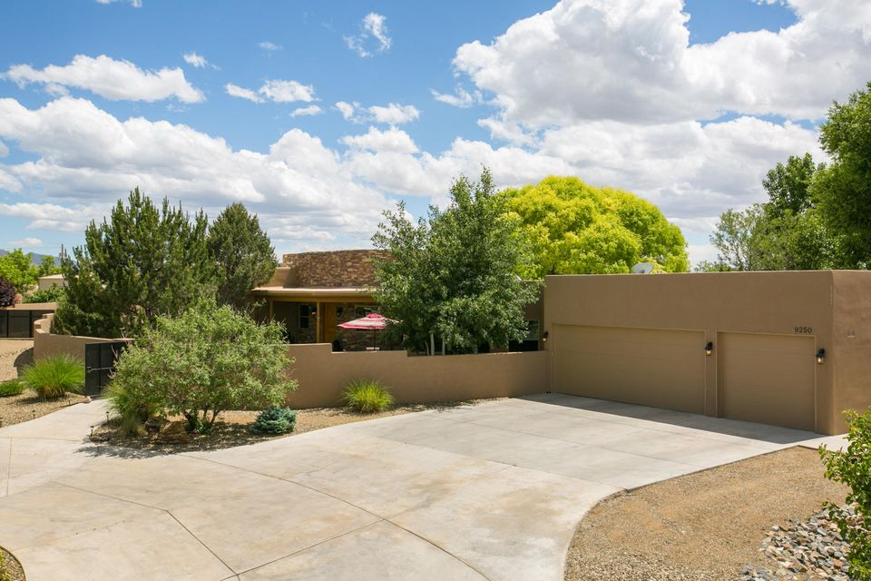 Highly desired location and school district in North Albuquerque Acres! Enter into this lovely, single level Southwest-style home through the landscaped front courtyard. Upon walking through the front door you are welcomed by an open living room and fireplace. The gourmet kitchen opens to a family room and doors to the expansive private yard with a water fountain, views of the Sandias, and where you will fall in love with the stunning tree that rests in the middle. Approximately 1 acre fully landscaped, outdoor living at its finest! Not only designed for entertainment, this home is also very family oriented with versatile bedrooms, an office, attached garage can fit 6 cars in tandem, and compound-like feel as the home is enclosed and gated at the beginning of the large roundabout driveway.