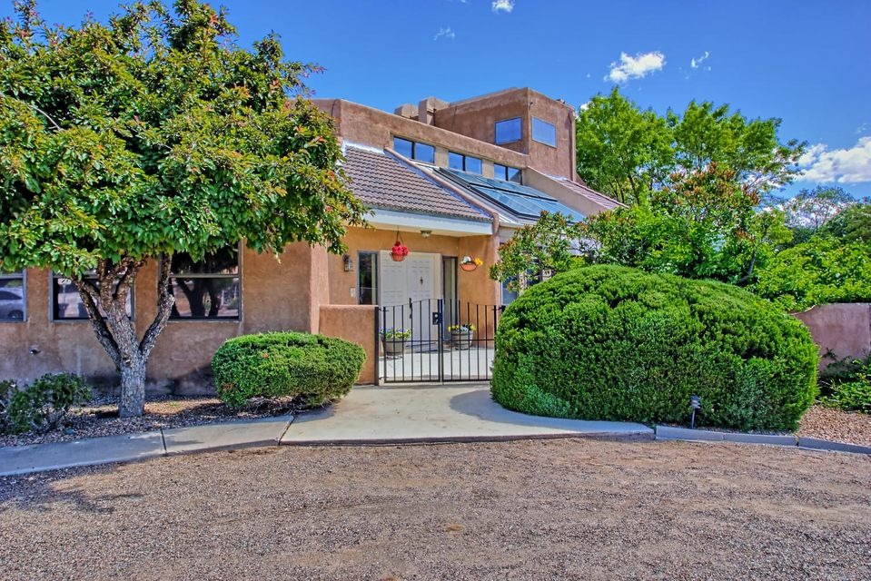 This gracious home is a peaceful oasis just steps away from the Bosque, River and Asecia trails. Located in a quiet neighborhood, this contemporary style home features a stunning two-story passive solar solarium with the soothing sound of a gentle water fall. The updated kitchen is spacious with updated stainless steel appliances and a wonderful island for prep or dining. Enjoy outdoor entertaining in the private back yard with a sparkling pool, Pool casita, outdoor kitchen and an enclosed porch for comfortable dining, serving, or relaxing. Room for everyone with 3 living areas, 4 to possible 6 bedrooms, 4 baths, and 2 car garage with back yard access. Enjoy all the charm, character, and Southwest living for a perfect North Valley lifestyle.