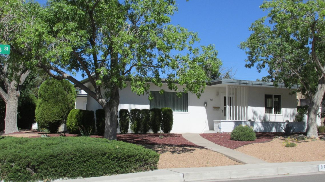 Mid-Century Modern large open, split floor plan, with 3 bedrooms & 2 baths in front, and 3 bedrooms 1 bath in back. Breakfast area in kitchen looks to outdoor living space in a private walled patio.  Separate dining area, ready for the family table. Two Spacious Family Living Areas, both with beautiful, custom brick fireplaces and built in shelving, one with Hard Wood floors. Good size bedrooms, and tons of storage. Over-sized two car garage to the back of house, with plenty of built in shelving for storage. Corner lot with large, Xeriscaped side and front yards w/ very little yard maintenance! Small back yard with a flower garden that can be easily turned into a fresh veggie & herb garden. Perfect for the family that doesn't have much time for yard work! Great price per Sq Ft in UNM Area!