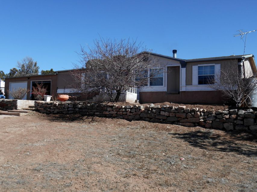 Nicely set up doublewide with two car attached garage on 17 acres, graveled driveway. Has retaining walls around home, landscaped with rose bushes and three fruit trees. This home has great views. Bring the Horses as this property has piped stalls with cover and plenty of pasture. Its full fenced and cross fenced also has some piped fence around the home. gutters are set up for rainwater harvesting and also has a permanent tank that can be pumped to water trees and bushes.