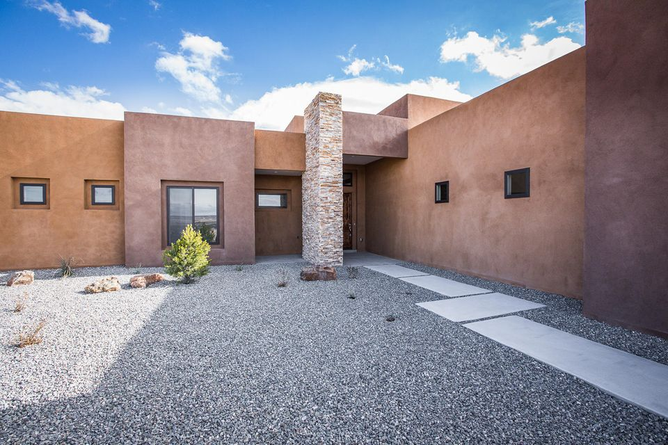 Beautiful New Custom Built Modern Pueblo Style Home. Incredible views of the Sandia Mountains and Santa Ana Mesas. This new beautiful custom home is situated on a fully foliated native lot with panoramic views. This Modern New Mexico Pueblo Style Home was built with all the high end custom features including custom, hand crafted cabinets throughout home. Large beams & tall ceilings with an open floor plan. Kitchen has a large butler's pantry. Interior walls are soundproofed in the family room and master bedroom. Incredible large windows taking advantage of Mountain views. Outdoor kitchen area with large covered outdoor patios. Back Porch is cantilevered to accommodate un-obscured views. Large 3 car garage fully insulated. A one of a kind custom home.Great discount on this Model Home!