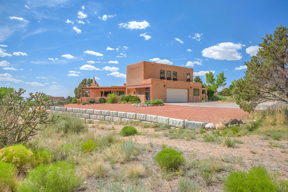 Contemporary SW style cstm home on a great view lot w/exceptional vistas from mountains to city. Super low maintenance with deer & birds passing by- a true nature wonderland. Within walking distance to the Sandia Mtn Wilderness & yet only minutes to shopping, coffee shops, etc. Well maintained & upgraded by proud owners. Extremely open & fnctnl layout w/kitchen, dining & great rm all open to one another & all w/awesome Sandia mtn views. Chef's kitchen & mstr ste really make this home special- hard to beat the natural light & views! Inside you'll be charmed by Saltillo & hrdwd flng, expsd adobe accent walls, nichos, hand-finished beams & corbels plus an inviting Kiva FP. Add to that an impressive handmade Sapele wood staircase & southern pine front door. An extremely warm & inviting home!