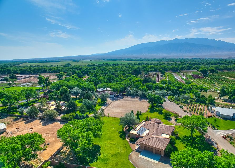***NOT ONE BUT TWO EXQUISITE HOMES*** Located in the beautiful Corrales Del Norte with 4.45 continuous acres! Perfect buy for multi family use as well! Over 9,000 sf of living space with 7 bedrooms, 7 bathrooms, 2 half baths, 5 garage spaces and 2,400sf horse barn has 8 large stalls, 2-bay wash stall, huge tackroom, auto fly spray system & roping arena. Gourmet kitchens with all the upgrades! Two Gorgeous, resort-like master retreat has wood, tongue-in-groove and beamed ceilings, fireplace, huge, built-in sauna, and new jetted tub with interior lighting. Guest en-suite has spa-like bathroom. This is to good of a deal to pass up! Homes are also listed separately.