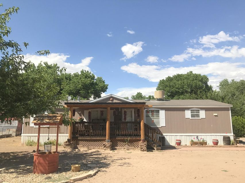 Enjoy the rural atmosphere of lush green east Corrales while keeping close to amenities in this beautiful setting. This doublewide mobile home in the heart of older Corrales is on a permanent foundation and has a covered front wood deck of quality and utility. It features two living areas and a formal dining room. The master bath has a spacious soaking tub and dual vanities. Just a short hike to the trails and river, this is one-of-a-kind!
