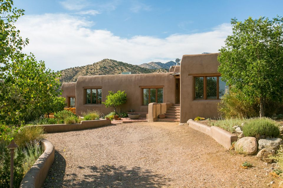 This classic Adobe, built by the acclaimed David Peterson is your quintessential Northern New Mexico home. Nestled in the foothills of the Sandias, the panoramic views are stunning. The home greats you with the finest touches. Solid wood gates and doors hand made by the builder are the perfect accent to the brick floors.  The home is equipped with a passive solar design as well as radiant heat for absolute comfort. The bedrooms boast closets all designed by California Closets, to maximize the space.  The open concept chefs Kitchen is perfect for entertaining family and friends.  Truly a one of a kind home.