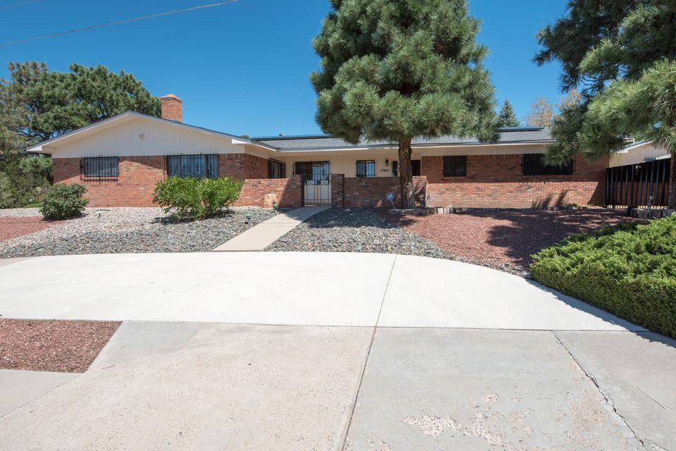 Beautiful single level 5 bedroom brick home in Foothills with 2 master suites plus 300 s.f.casita built in 2010. Informal and formal dining plus formal living room and great room. Lots of updates: Refrigerated air; roof warranty; no carpets. New electrical upgrade, water heater, furnace. Solar system bought for $30,000!  Large kitchen with beautiful restored wood cabinets. Large corner lot with fruit trees, shed and possibly room for pool. RV pad and extra parking. Owned solar system on new roof. Casita is a comfortable living unit with refrig air. Security system and security bars. Covered patio is secure enclosure; have small children or dog? Perfect. Shed conveys. Easy access to I-40 off Tramway. Near Kirkland, Medical Centers and UNM. No HOA.