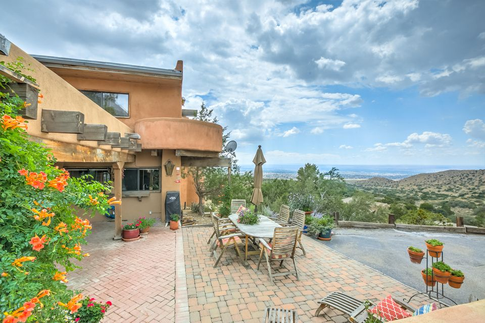 +++++ Over 100,000 price reduction +++++Spectacular and breathtaking views from this gorgeous adobe home situated high above Albuquerque. Over-sized wood beams. Recently refinished brick floors, wood floors and new carpet add to the cozy and warm welcoming atmosphere of the house. Enjoy spectacular sunsets, snowfalls and all the wildlife that this tranquil setting has to offer. Master has sweeping city views to wake up to every morning, and a walk out balcony to enjoy your morning brew. In-law suite optional. The house is the perfect setting for entertaining family and friends. This is a true one of a kind masterpiece that will take your breath away.