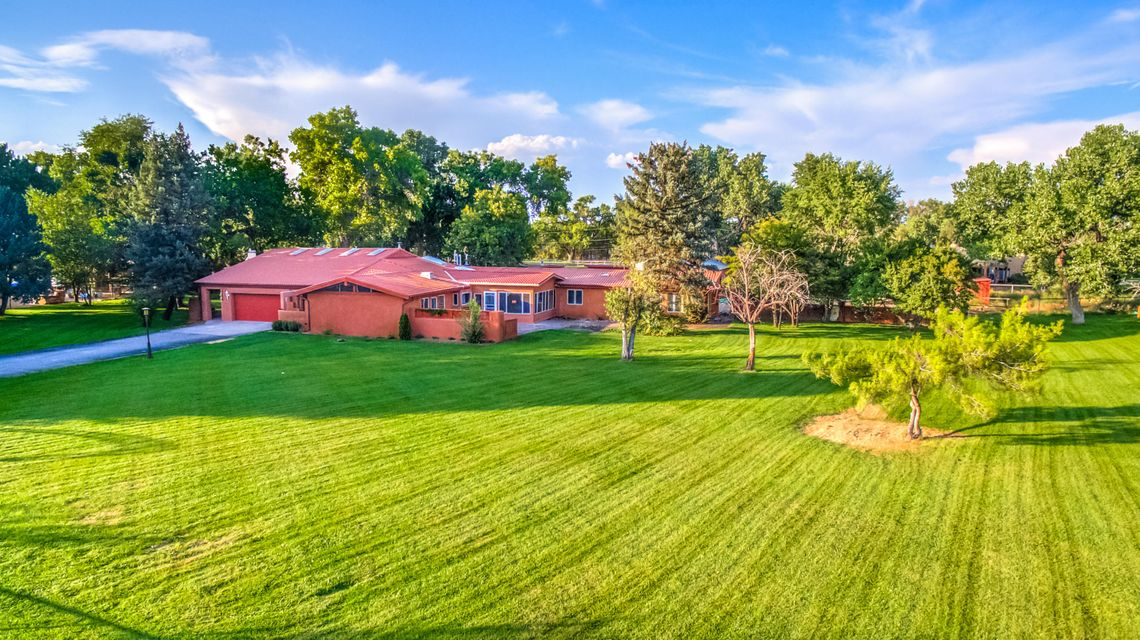 Offers welcome! Mid Century on acreage. Nestled under majestic cottonwoods on 2.45 eastside acres.A recently remodeled 5BR, 5000sf home w/2 car gar, plus a 2BR 600sf casita, 1150 sf workshop w/bath.  Gated entry! New windows, floors, roof,& septic! Well designed for a large family w/high ceilings. Formal living,dining,fabulous kitchen w/ island, granite, SS appliances. Open to FR w/FP. Media room, studio room, great laundry room. MBR suite w/sitting area, walk in closet & workout area! Separate 3BR/Bath wing plus 1BR/bath area. New wood & carpet floors, simply beautiful. Corrales Road access for casita.  Workshop fits several cars! Area for horses! A great property!  Access to the Bosque for trails and open space! Popular south end Corrales location! A beautiful property!