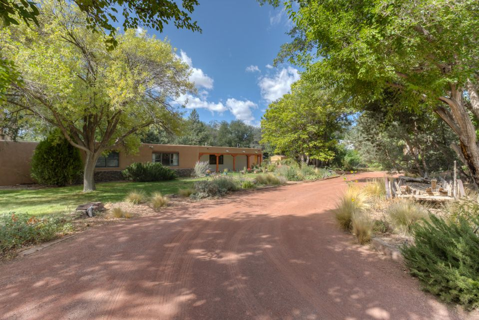 Serene setting, nestled in the Cottonwoods of Corrales. The moment you step onto the front portal this cozy Adobe home welcomes you in and beckons you to stay. Beautiful brick floors through the entire home. Gorgeous wood plank and beam ceiling. Three custom wood-burning  fireplaces, freshly plastered and painted. Kitchen is open to the dining room, family room and allows for entertaining. Master suite has an additional sitting room and fireplace. 3 additional bedrooms and an office/5th bedroom. Guest bedroom and bathroom on the west wing of the home, additional rec-room or could be converted back to a garage. Over an acre lot with a stable/tac room and horse arena or could be used for all of your outdoor ideas. Membrane roof, New septic system, updates to well, new electrical service. WOW
