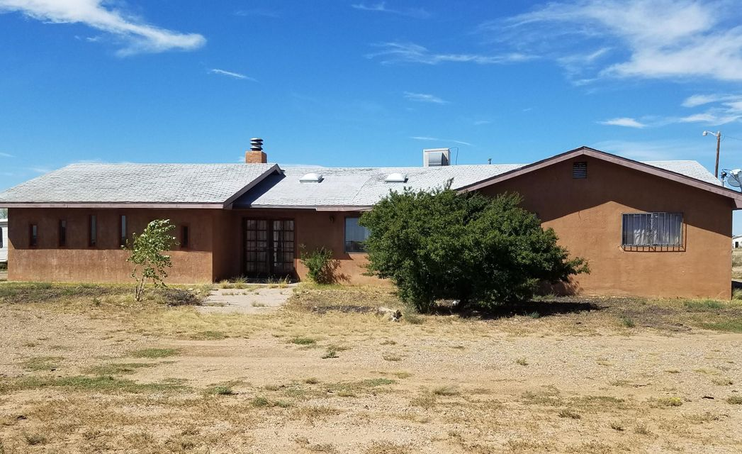 Situated on 2.68 acres on the east side of Los Lunas is this 3 bedroom, 2 bath custom home with workshop out back. Features include an efficient kitchen loaded with cabinets, large living room complete with wood burning fireplace, large utility room and additional storage space. The land is cross-fenced and level - a blank canvas awaiting your creative landscape design.