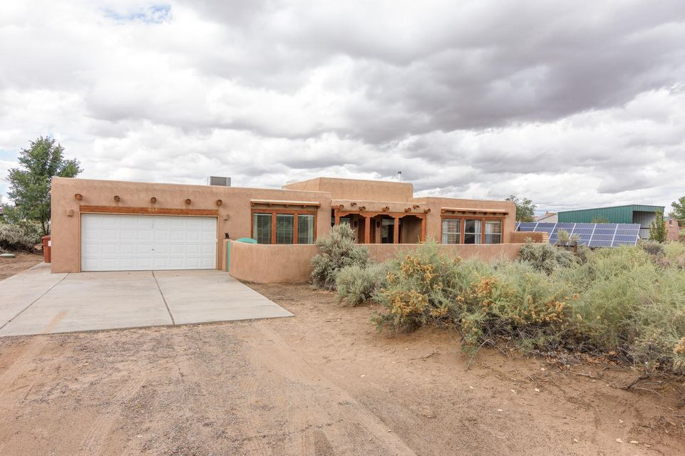 Southwest charmer located in the Village of Corrales, nestled on a .75 corner acre lot with backyard access & RV parking! Courtyard entry capturing awesome views of the Sandias invites you into a bright & spacious home; enhanced with stylish updates & southwest touches, beams, corbels, vigas & exposed adobe! Great VIEWS from living & dining room! Pellet stove!  Generous size kitchen with stainless steel appliances, abundance of cabinetry! Handsome laminate wood floors! Master offers wall of windows w/views & master bathroom has jetted tub, separate shower & walk-in closet! Fantastic separated game room has adjacent 3/4 bathroom, with door to back patio, perfect for possible in-law/teen quarters! NEW TPO roof (2014) w/warranty! HVAC heating/refrig. air! Owned SOLAR panels! No utility bills!