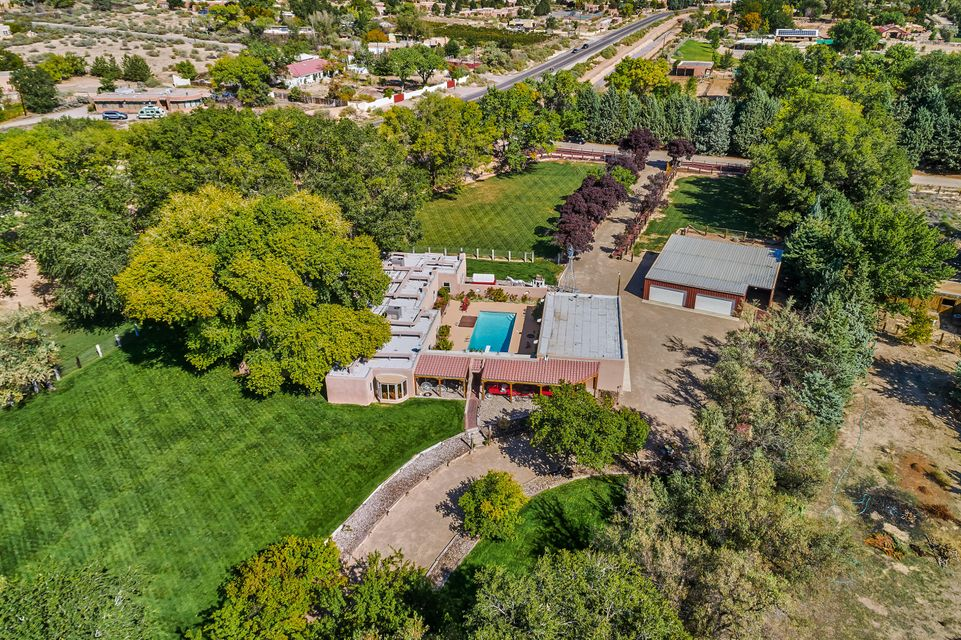 Extraordinary hacienda estate on over 2.5 lush acres w/ mature cottonwood trees, flowing gardens, acequia rights, 8-car garage, 5-stall barn, stable & gorgeous pool, all situated in an oasis-like setting on the south end of Corrales close to all amenities. Santa Fe-style adobe home is full of character w/ viga & latilla ceilings, brick & wide-plank pine floors, 4 kiva fireplaces & country kitchen that opens to serene portal w/ 100-yr old cottonwood tree & charming screened-in porch. Updates include new roof (2016), re-surfaced pool & deck, 2 new HVAC units, new bay windows & 2 new septic systems. Private setting close to walking/horse trails in a property ideal for entertaining or enjoying your animals. Corrales country living at its very best!