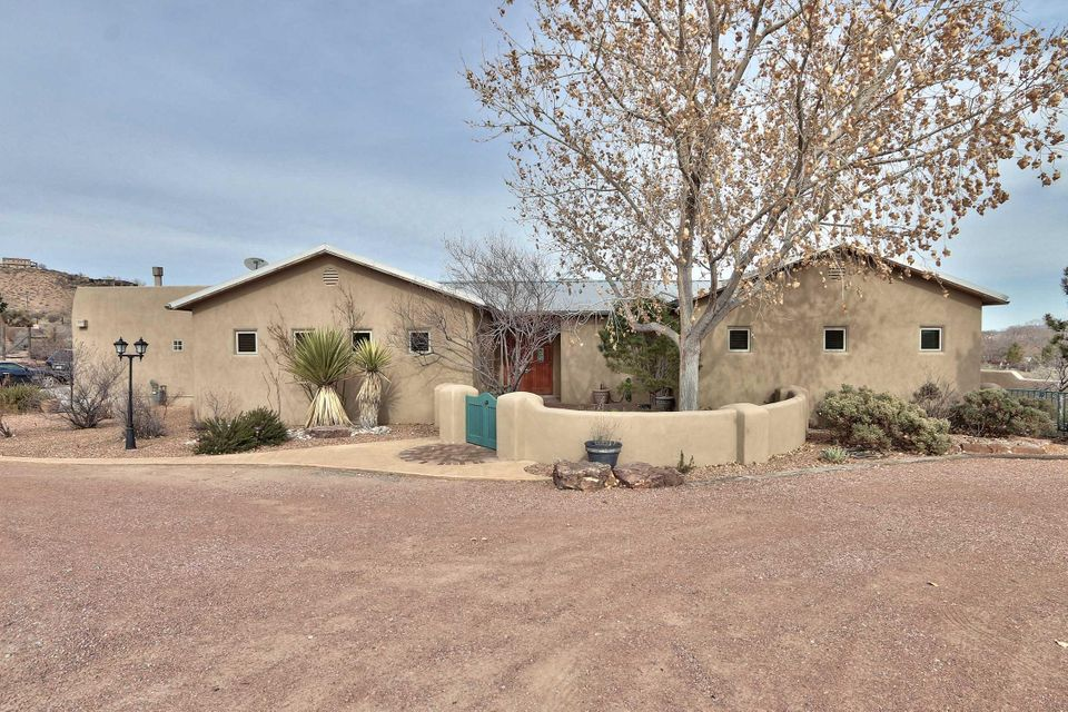 Gorgeous custom built move in ready one story home in Corrales, w/stunning Sandia Mountain views, Open Floor Plan, 24X23 FR, high tops, Stainless Steel Appliances, walk in Pantry and extra Wine Room w/storage.  Built in shelves in the main living study/office area for entertainment system, Gas Log FP, in main living area and office. The private Master Suite includes a sitting room with Gas Log FP, luxurious jetted tub, his/hers walk-in closets. A second Master Suite has a private entrance which makes a great guest quarters.  The home has a finished three car garage w/built in cabinets. Huge 0.98 acre lot; landscaped yard, covered Patio w/FP makes for entertainment and private enjoyment.