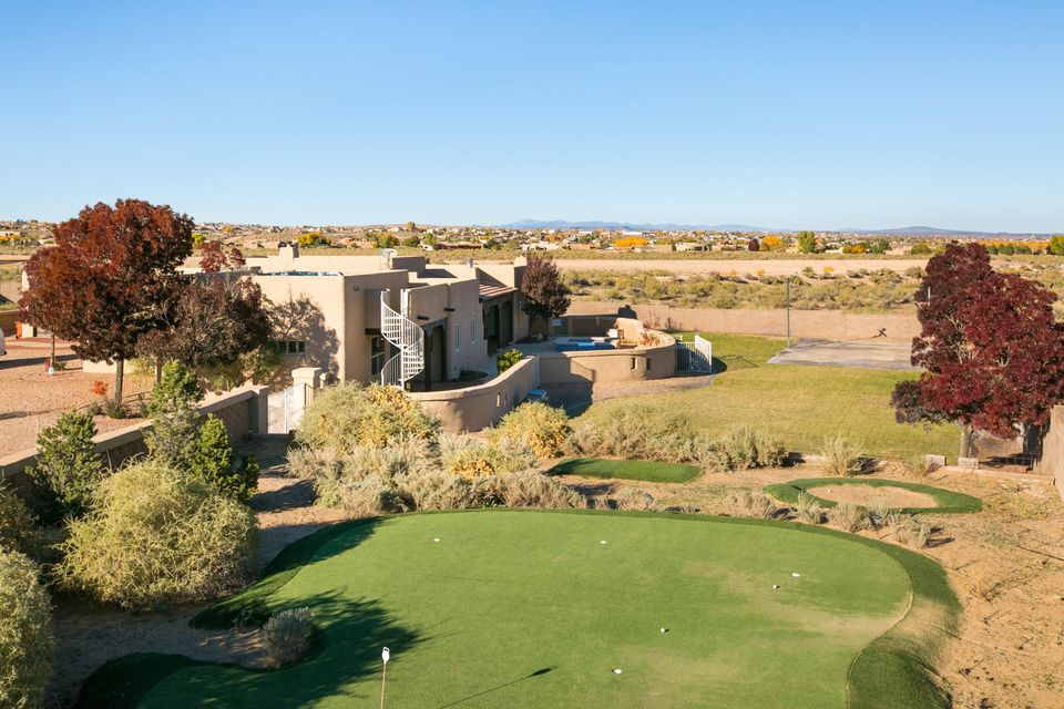This is the whole package! An incredible property nestled on an amazing 1.17 acre lot w/phenomenal views, outdoor living spaces & loaded w/charm & amenities. Spacious living room with gorgeous beamed ceilings & a stone fireplace. An Elegant dining room perfectly situated next to the gourmet kitchen w/granite counters, center island cooktop, loads of cabinets & a breakfast nook. Luxurious owner's suite with a Kiva fireplace, sitting area & backyard patio door to the pool/spa. 2nd and 3rd bedrooms feature a Jack & Jill bath & 4th bedroom/office has a large closet. The game room/rec room boasts raised ceilings, pool access & a roof top deck! there's MORE-a putting green, lighted sports court, pool  & spa, outdoor Kiva, fire-pit, grass for kids and/or pets & a batting cage! It is a DREAM HOME!