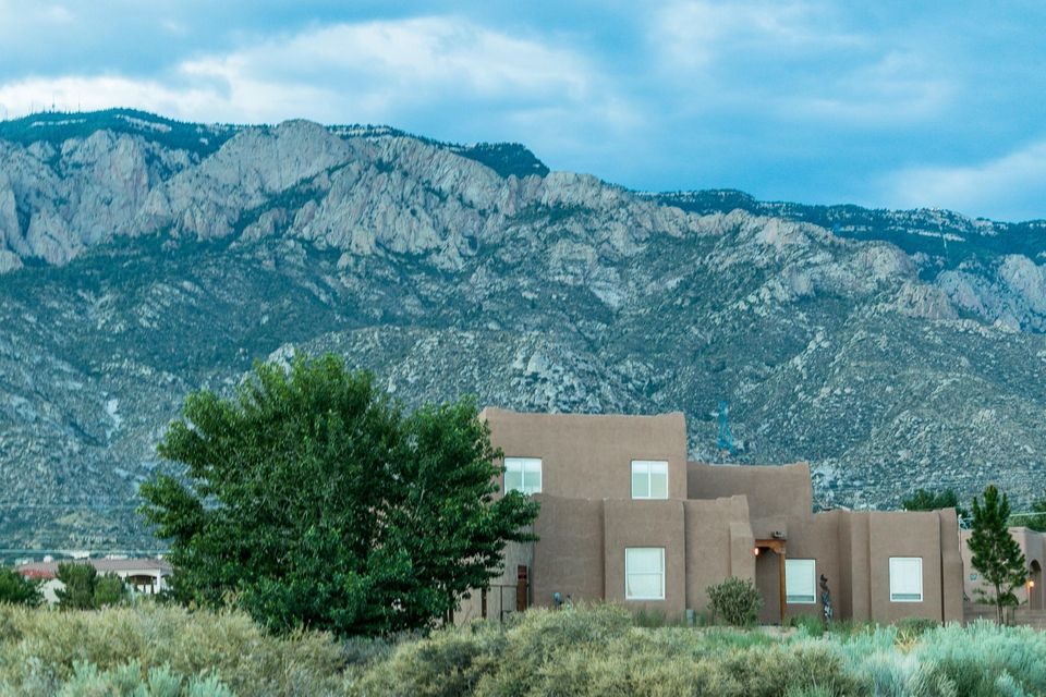 Stunning views of the Sandias & close to hiking/biking trails in the foothills! Strategically positioned on .89 acres to capture exceptional mountain views, this well-thought out home is the ideal blend of comfort and extravagance. Even if you are working in the well-appointed kitchen w/ granite & stainless steel appliances, you will still be spoiled by the views! Luxurious master suite on main level & separate from other bedrooms. Two addl bedrooms & bath, plus 2 living areas, formal dining & office on the main level. Upstairs enjoy spectacular city lights & mtn views from the 2nd master bdrm/guest suite or teen-ager's dream room with loft/study area & bathroom! Horse stall, private backyard, 3-car garage, your own well (not shared!) & sought after area make this your ideal next home!