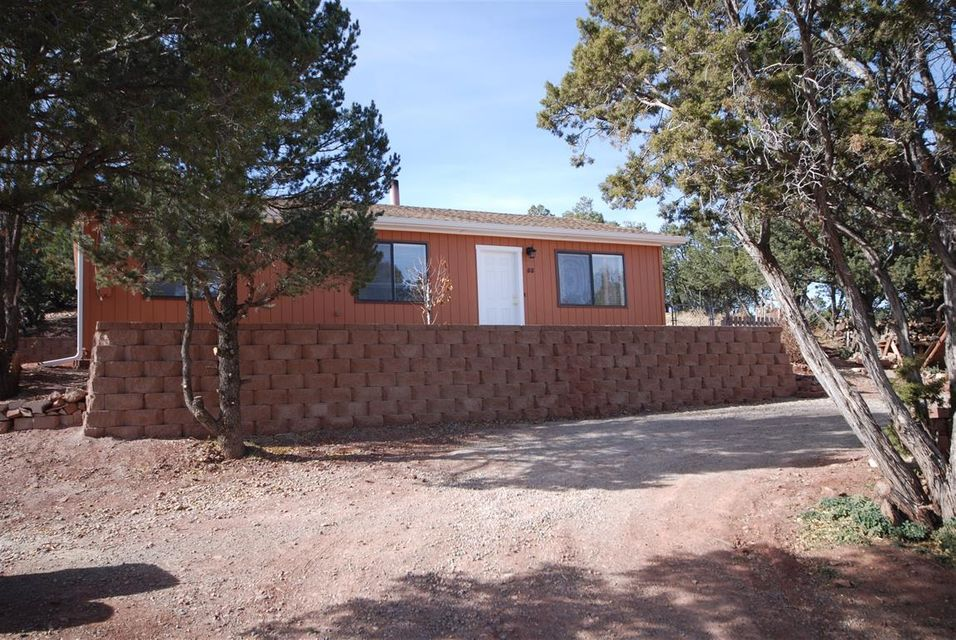 Absolutely darling small home at the end of the road in Sandia Park.  This home has been totally redone from top to bottom.  Beautiful tile floors, raised ceiling and new cozy wood stove in the living room.  New cabinets, countertops, sink, faucet in the kitchen.  New entry doors, all new hardware, light fixtures, ceiling fan,carpet, sinks, faucets, heaters, toilet, tub surround, blinds.  Not a thing left to replace or even paint.  Outside has new paint, gutters, roof, septic, gravel surround.  The block retaining walls alone were $10,000 and create great garden areas.  Property adjoins a tract of land that isn't developed and there are trails out the front too.  Connected to Sandia Knolls water system and a brand new septic system. 8X12 matching shed. This is a peach and won't last long
