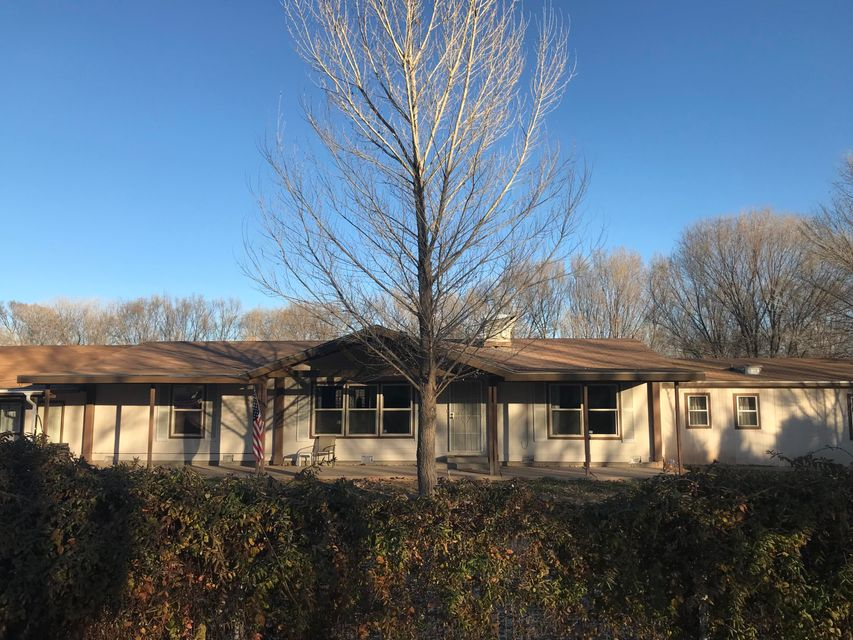 Come and see this 4 bedroom, 2 bath, property on over an acre, in the Los Chavez area. This home features a 23'x28 Garage with shelving, bar and entertainment furniture, and a 23'x11' Bonus room. Inside you'll find a cozy wood burning fireplace, next to the open living/dining area, as well as vaulted ceilings, and both wood laminate and carpeted flooring. The exterior features a huge covered back porch, and a covered front porch. 2 Master BRs, 1 has it's own entrance. Fully fenced/gated lot. Fruit Trees, and room to add a shop, a garden, or horse/animal pens. Room for kids! Appliances include dishwasher, oven, microwave, garbage disposal, and window ac units... tons of storage! Very few like this one for this price. Come and see it before it's gone!